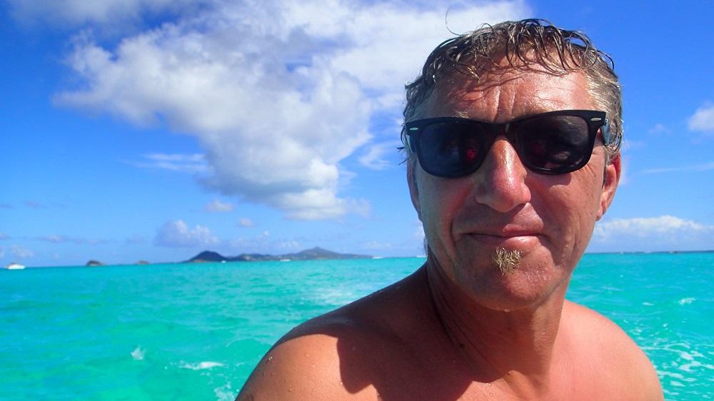 Jörg beim Dinghifahren in karibischen Traumwasser