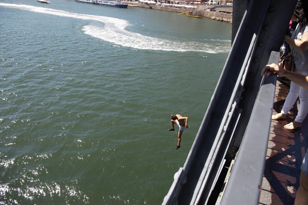 Jugendliche springen für Touristen waghalsig in den Douro