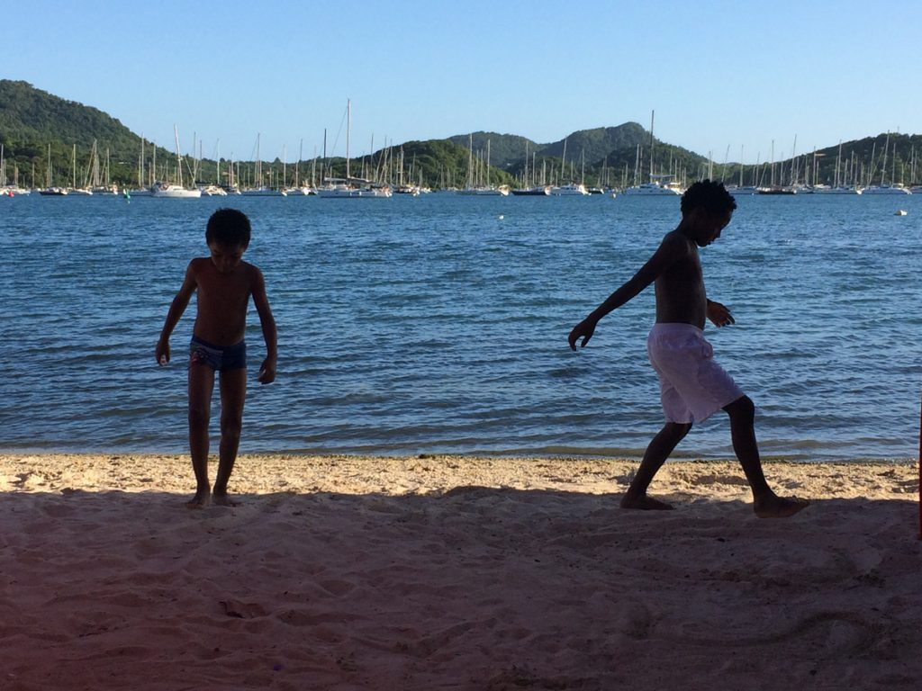 Einheimische Kinder spielen am Strand mit Blick auf die Bucht von Le Marin
