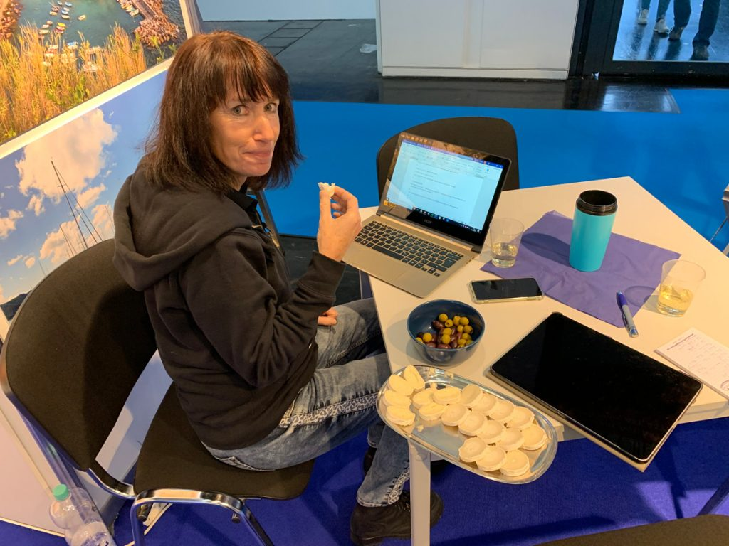 """Karin versucht auf der Messe 2020 """"nebenher"""" die wichtigste Büroarbeit zu erledigen"""