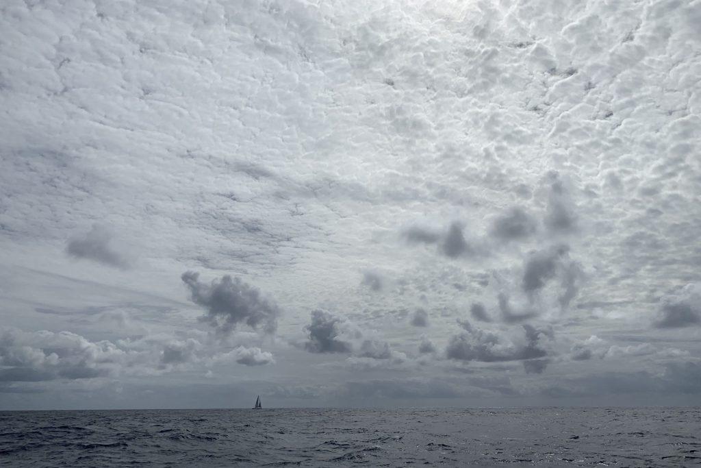 Faszinierendes Wolkenbildung in grau mit anderer Yacht am Horizont